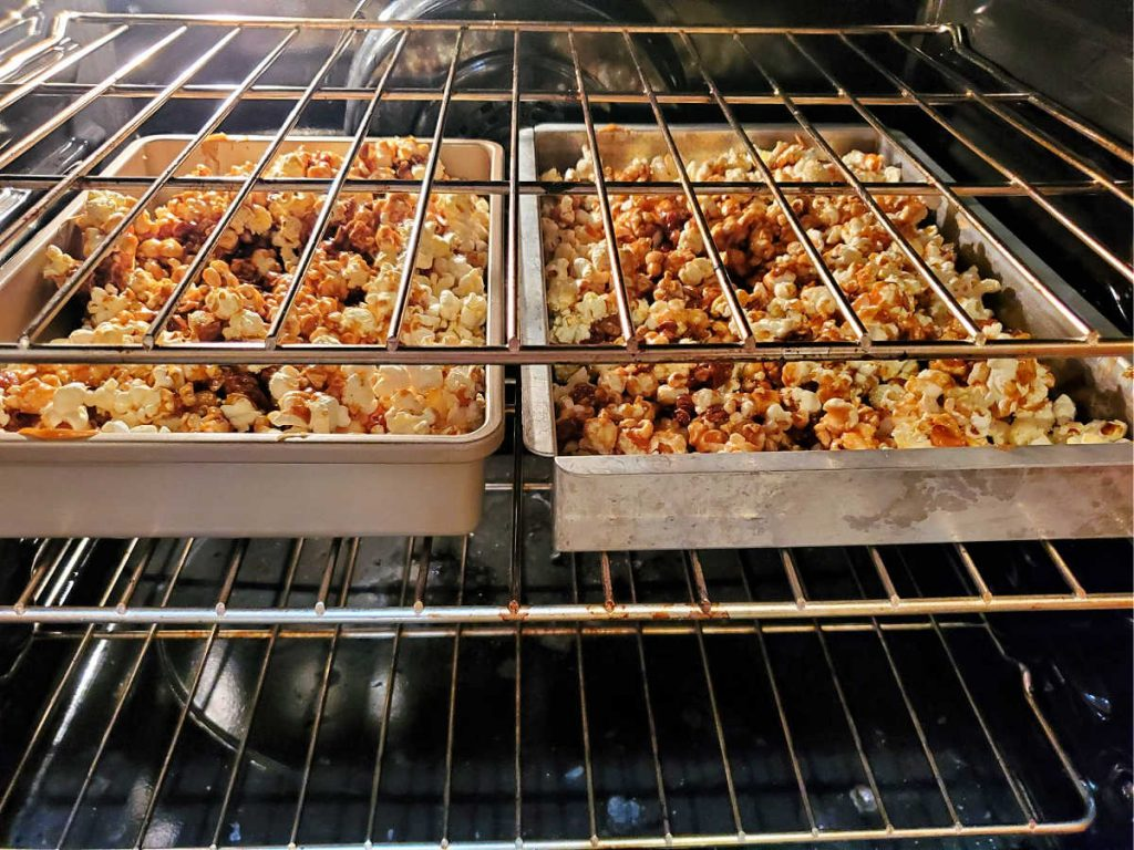 2 pans of caramel popcorn in the oven.
