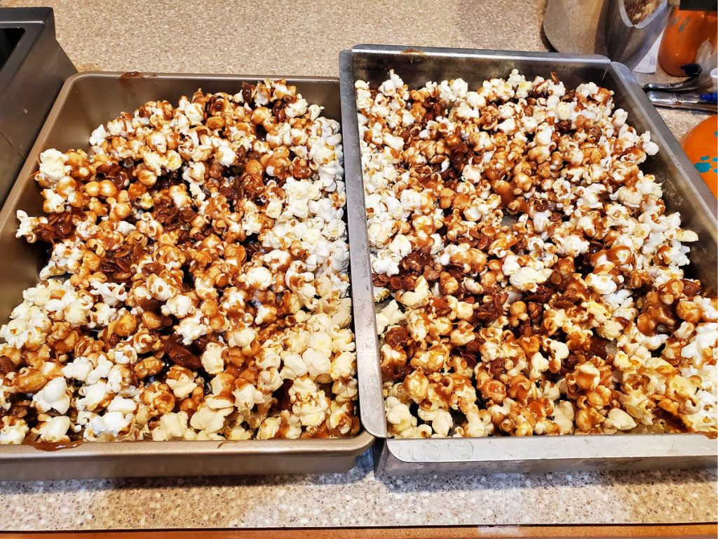 Two pans with popcorn, candied pepitas, and caramel.