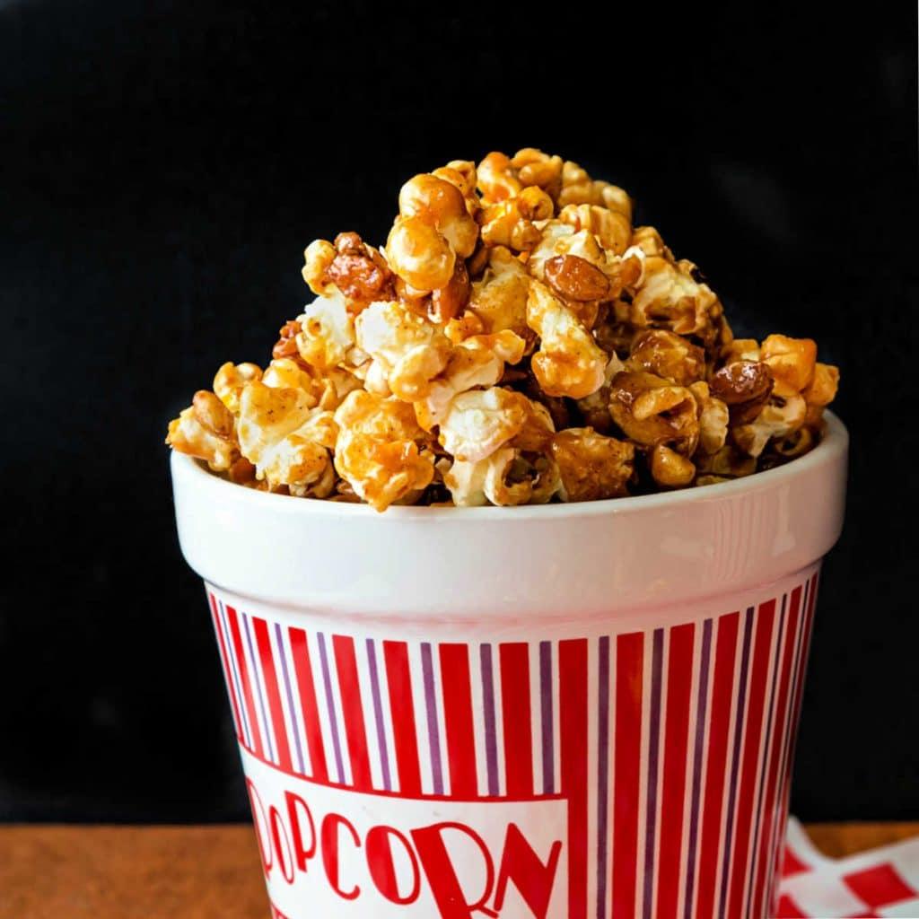 A ceramic popcorn container full of pumpkin spice caramel popcorn.