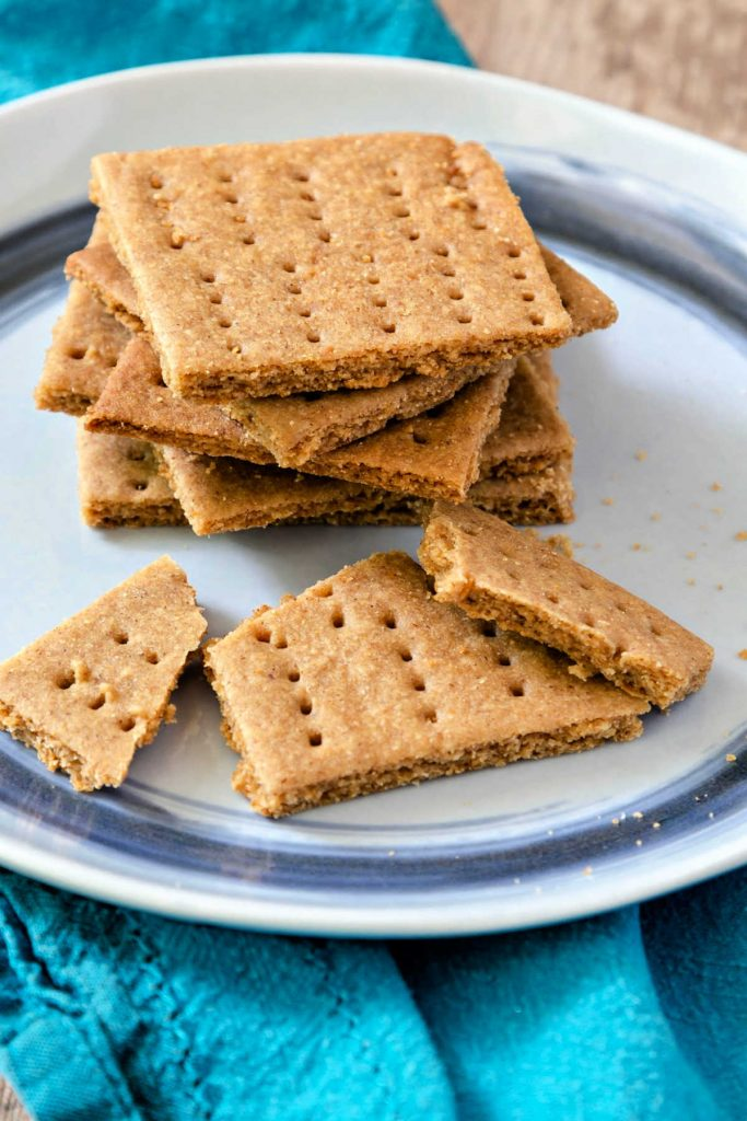 Homemade graham crackers stacked on a plate.