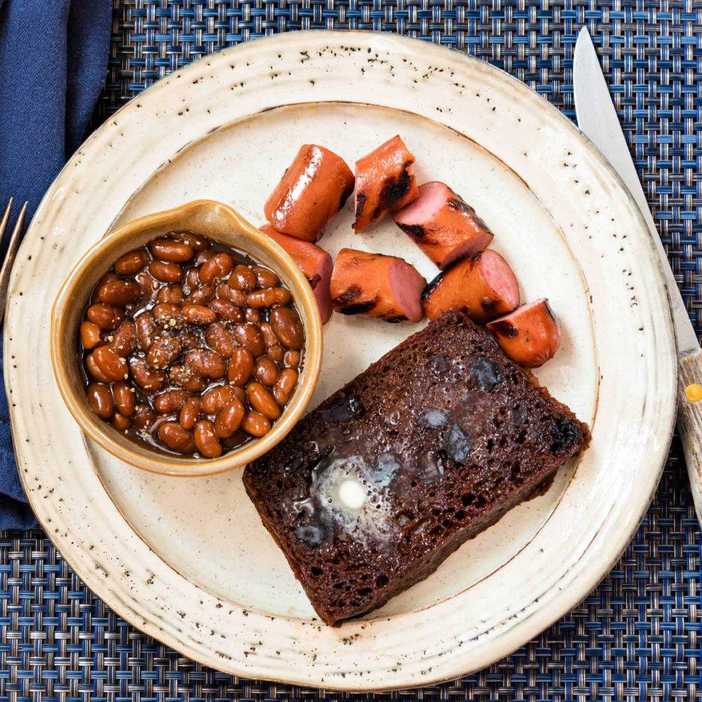overhead shot of Boston brown bread, grilled franks, and a bowl of baked beans