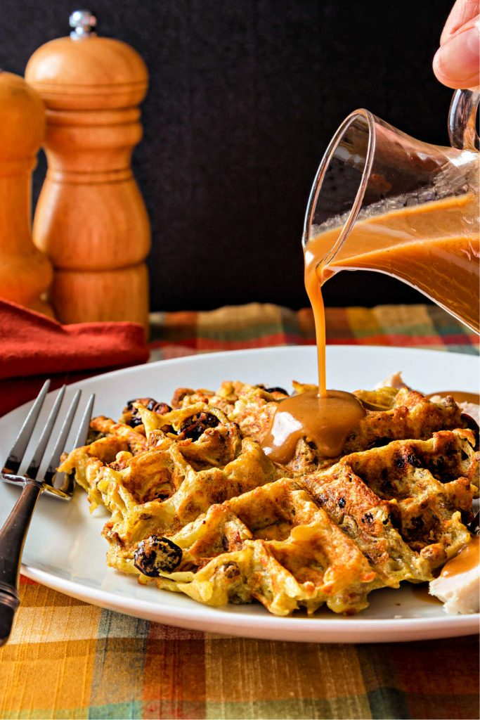 Gravy pour over a waffle made of potato stuffing on a white plate.