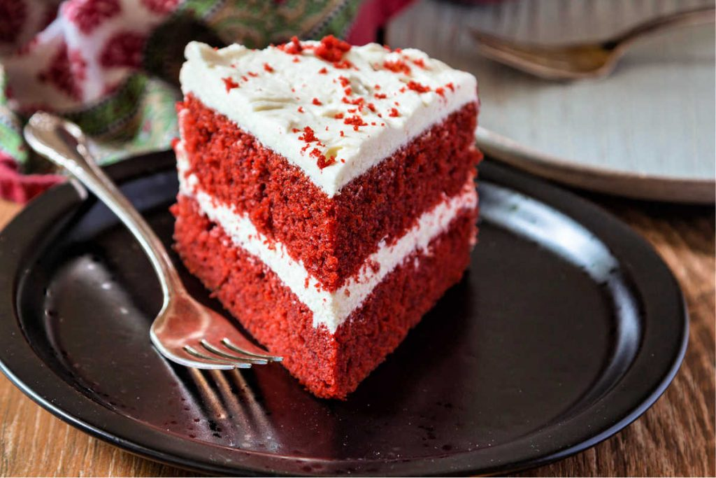 slice of red cake with white frosting on a black plate