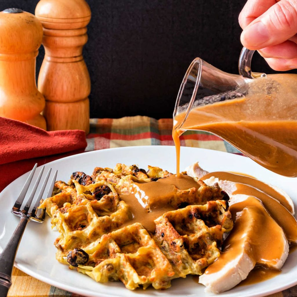 Gravy covered potato stuffing waffle on a plate with turkey.