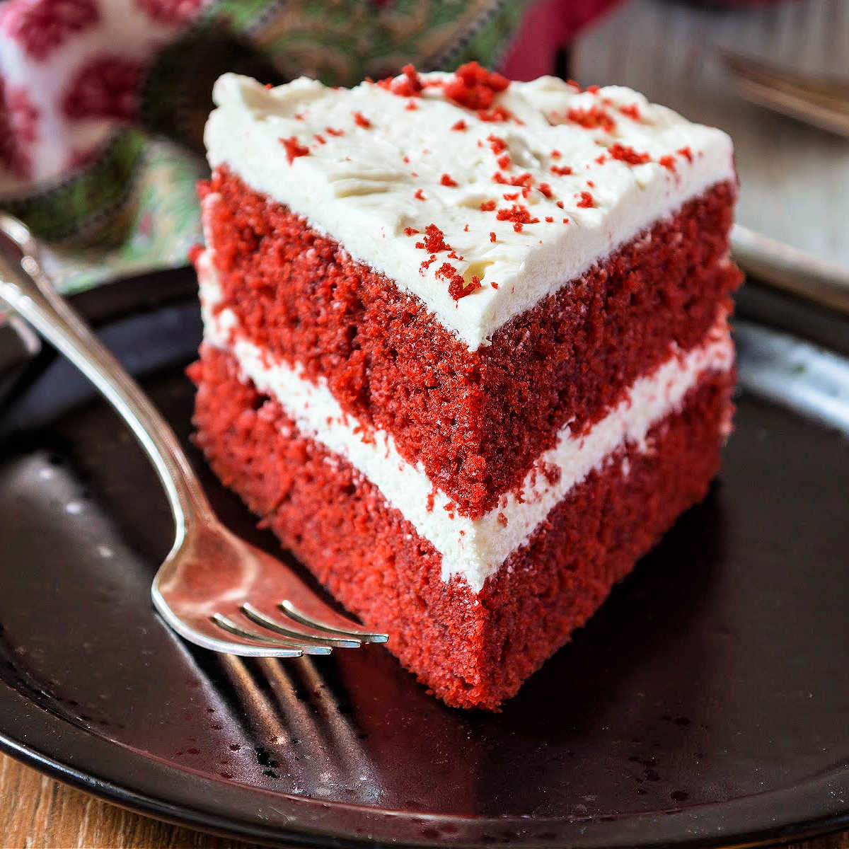 A slice of red velvet cake iced with white icing on a black plate.