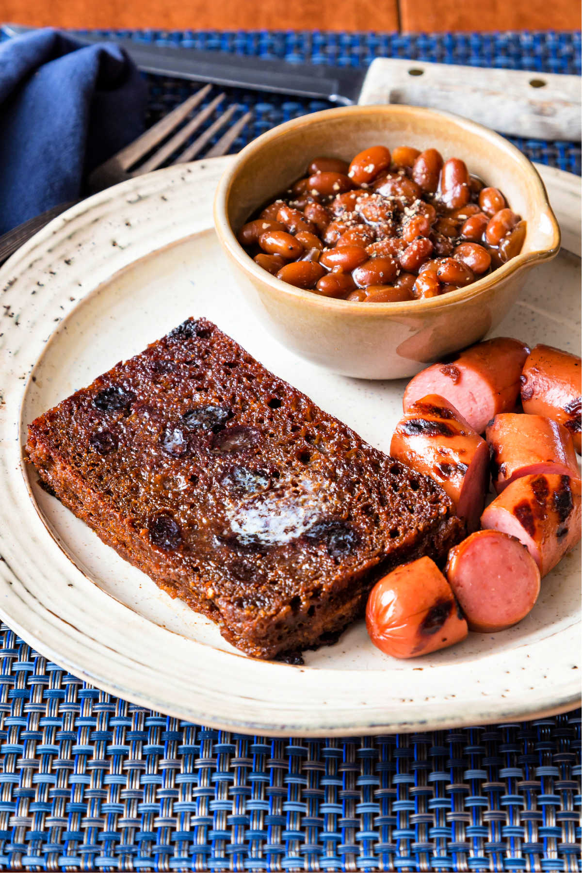 a slice of butter-fried Boston brown bread, franks, and beans on a plate
