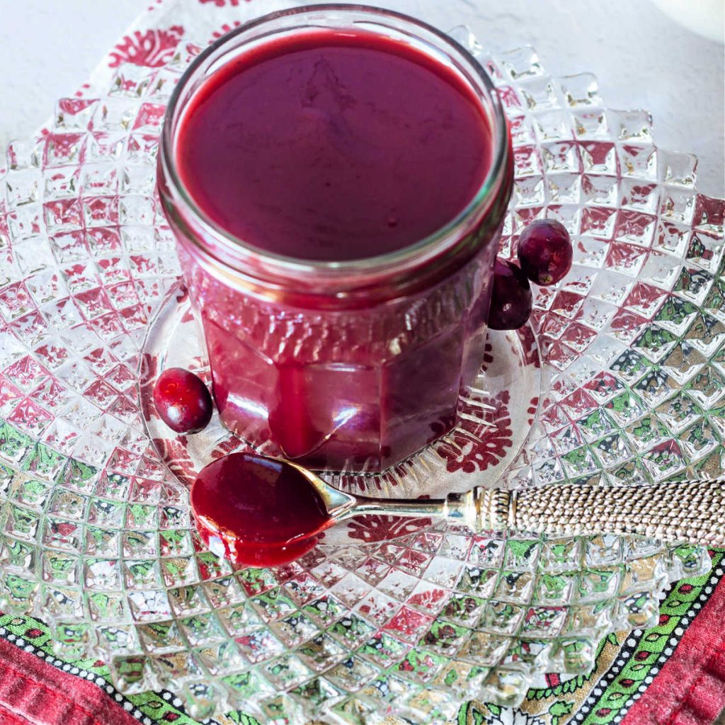 A spoonful of cranberry ketchup and a jar of same on a crystal plate.