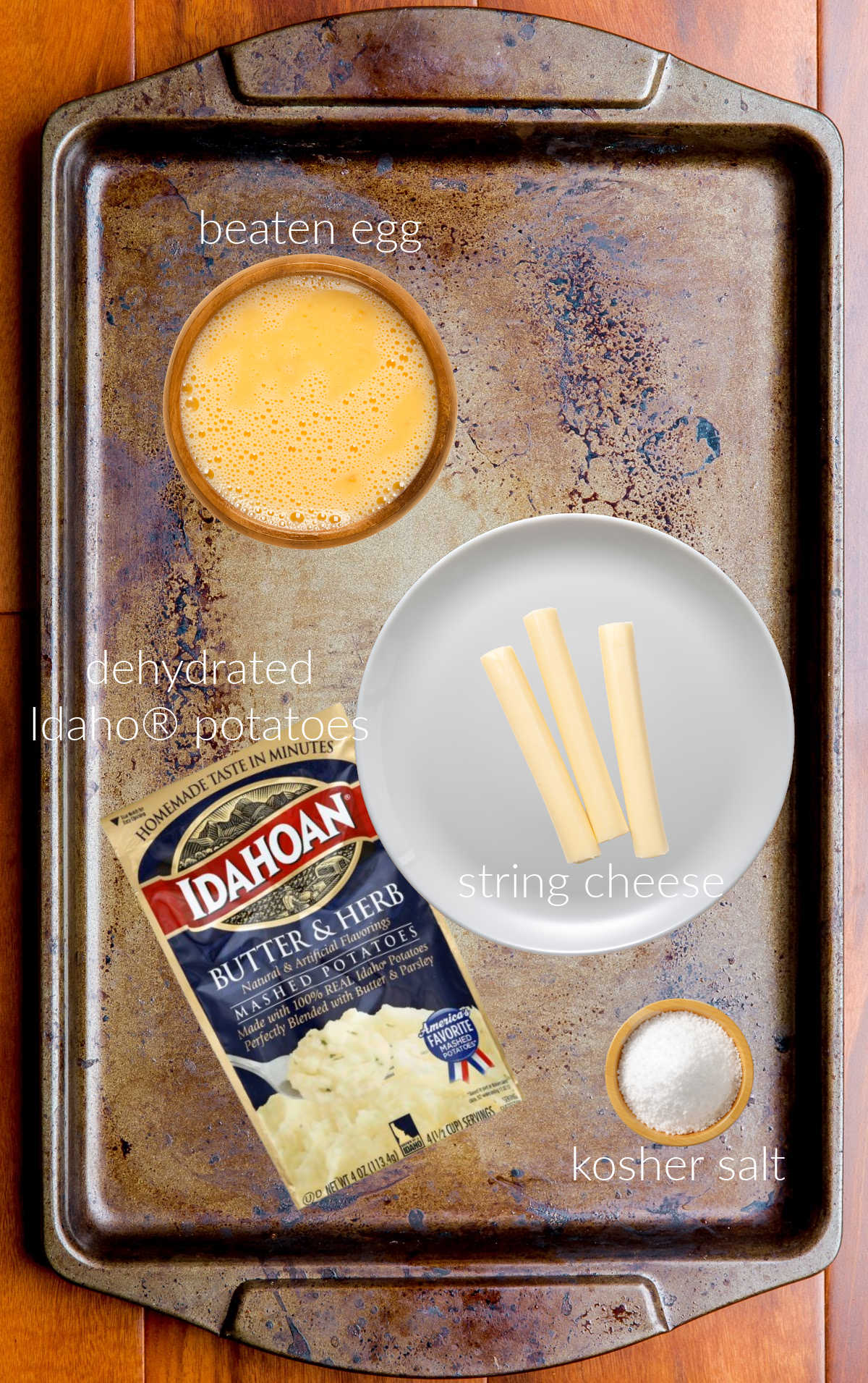 Collage of ingredients for making fried cheese sticks, laid out on a sheet pan.