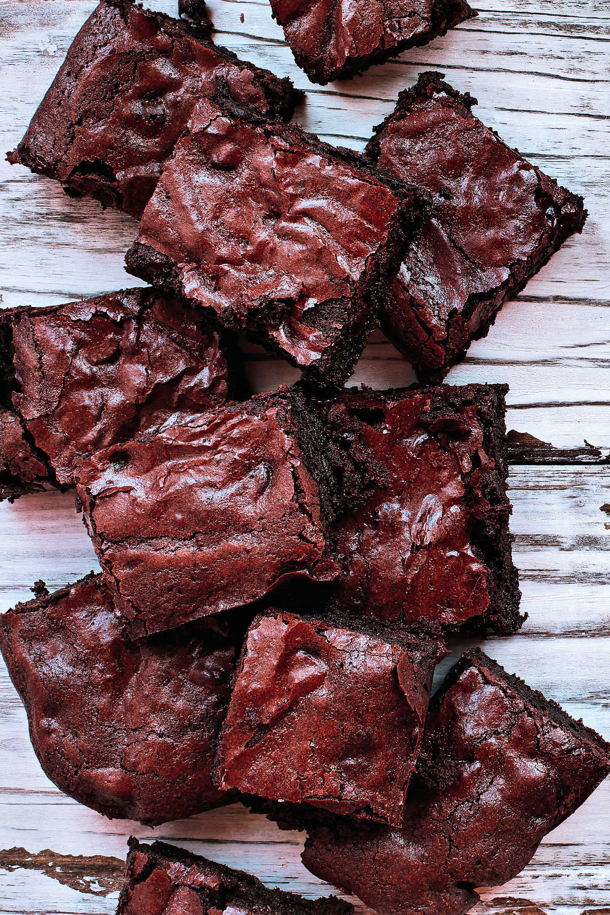 Squares of delicious, homemade cocoa powder brownies stacked on a white rustic wooden table background. Image shot from top view overhead.