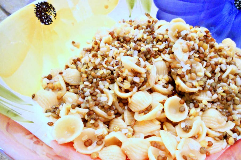 A bowl with cooked orecchiette pasta and lentils.