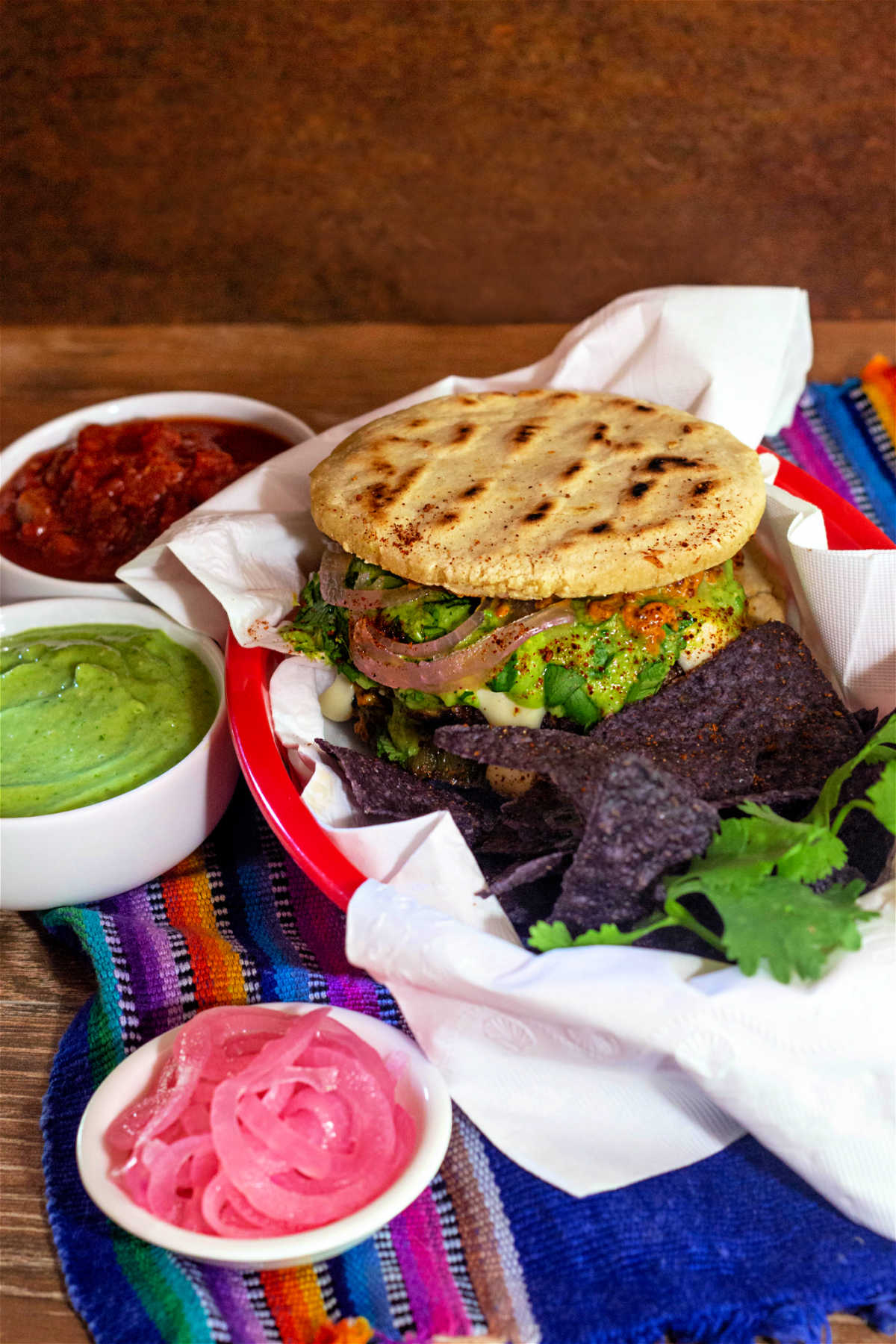 A burger with blue corn chips and ramekins of toppings.