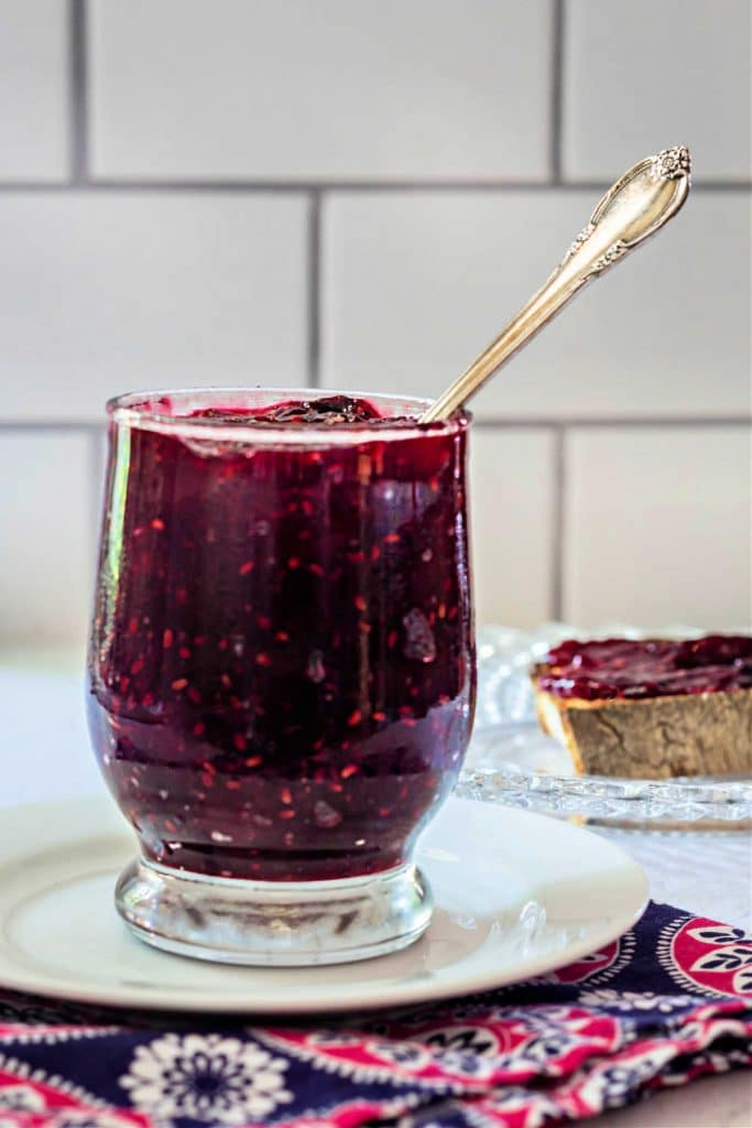 A jar full of mixed berry jam with a spoon in it.