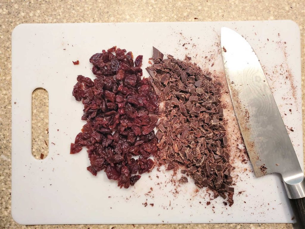 Overhead shot of chopped dried cherries and finely chopped dark chocolate.