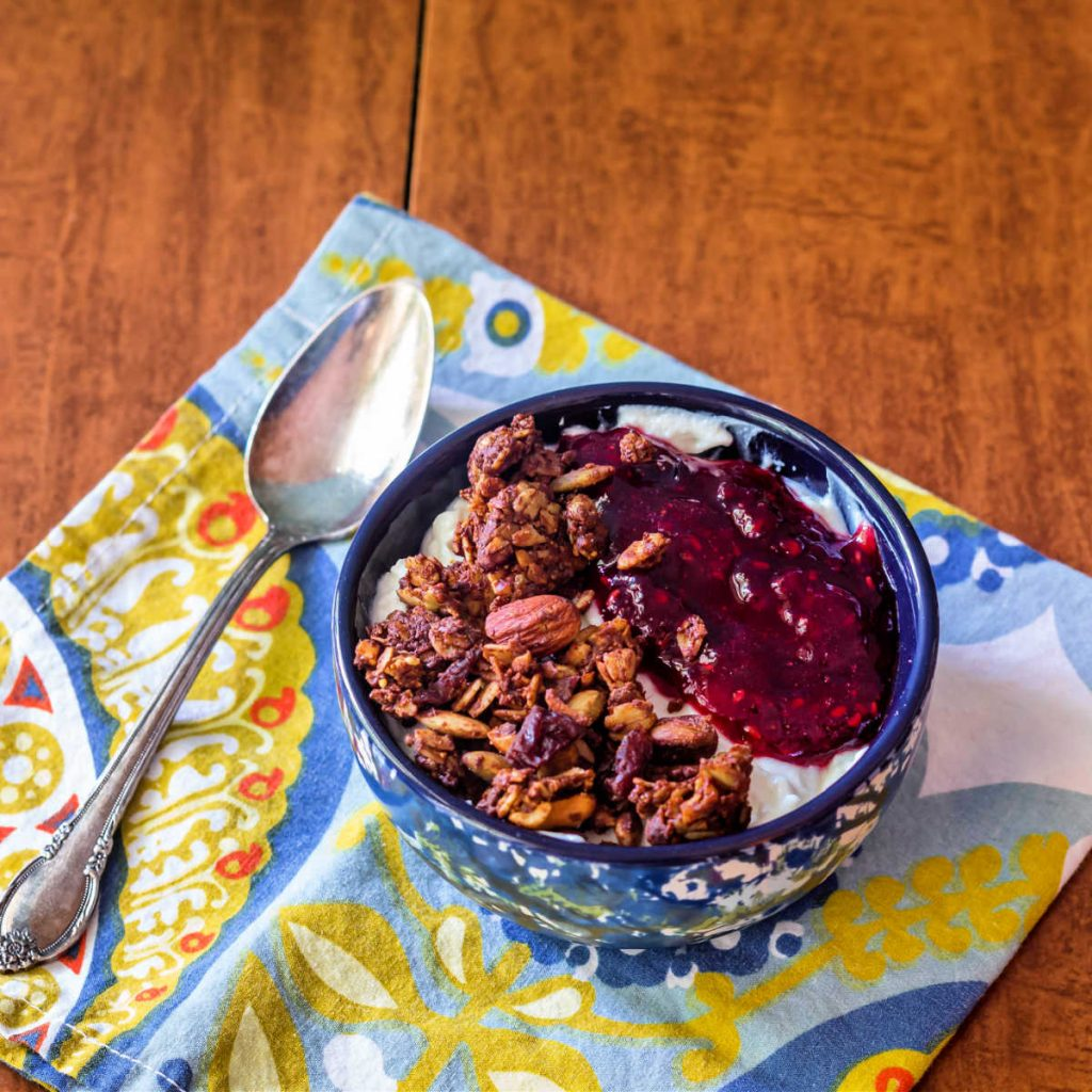 A bowl of yogurt topped with granola and homemade jam.