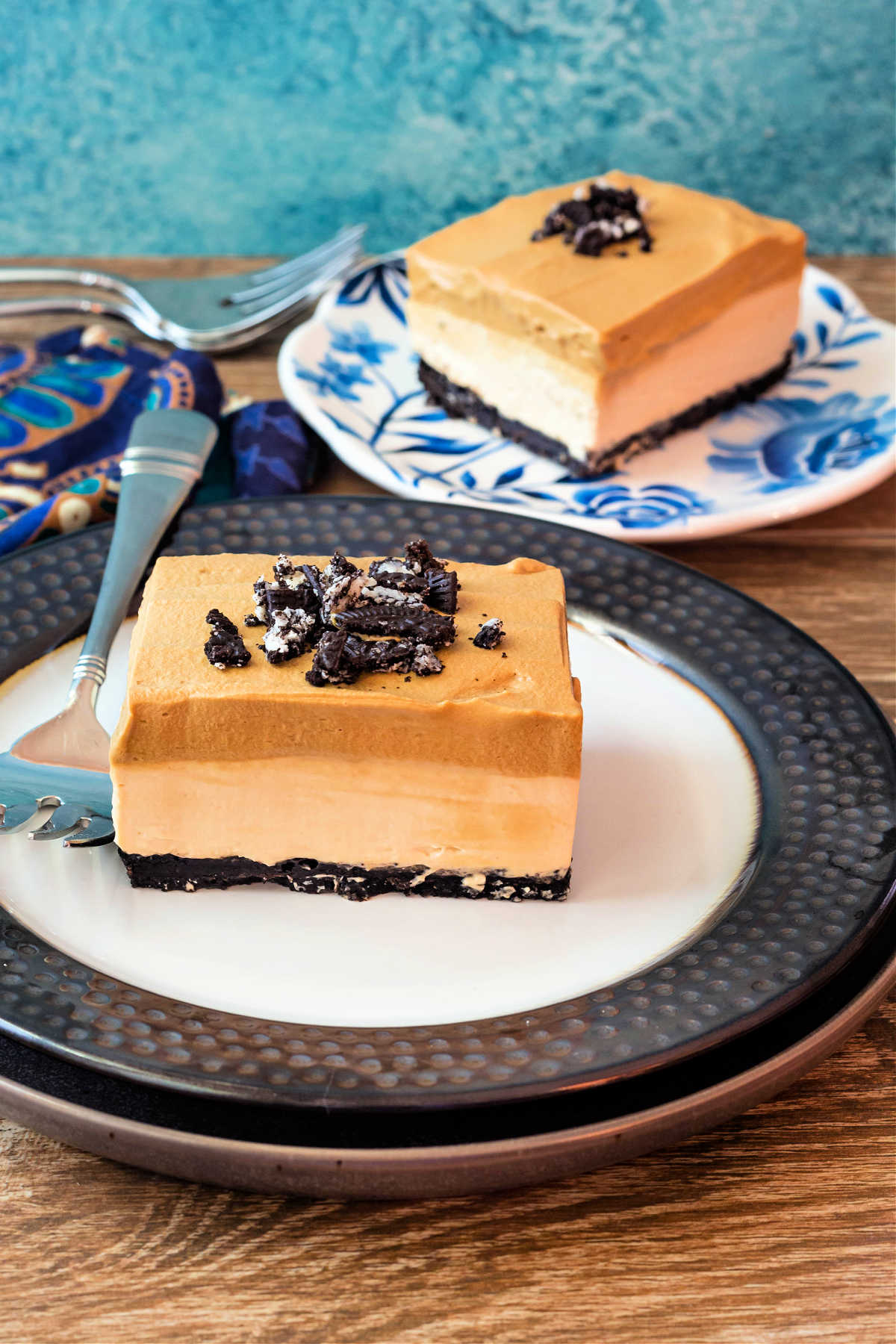 A vertical image with a square slice of dessert with chocolate crust, a tan cheesecake layer, and a darker tan whipped coffee layer topped with crushed chocolate cookies on a plate with a similar plated dessert in the background.