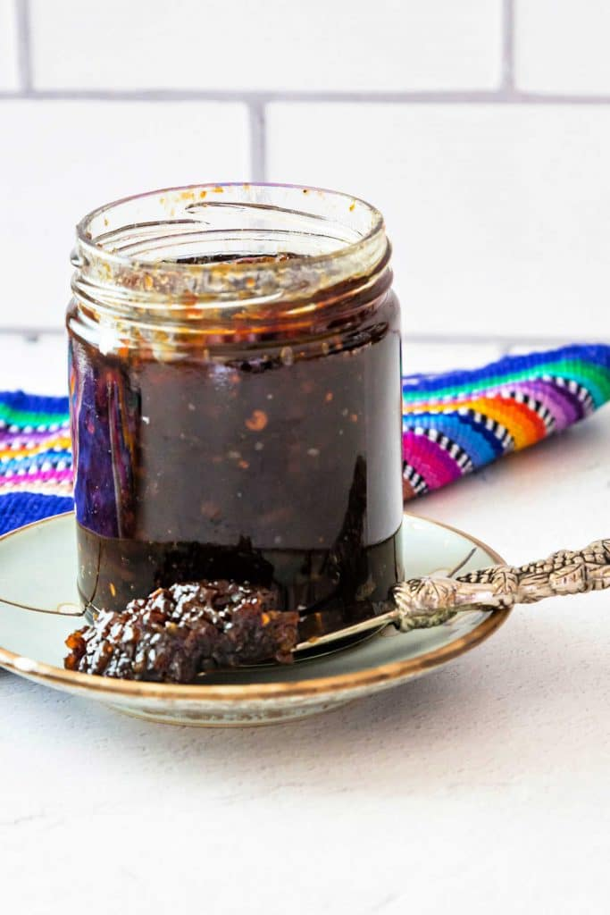 A jar of spicy bacon jam on a blue plate against a white background.