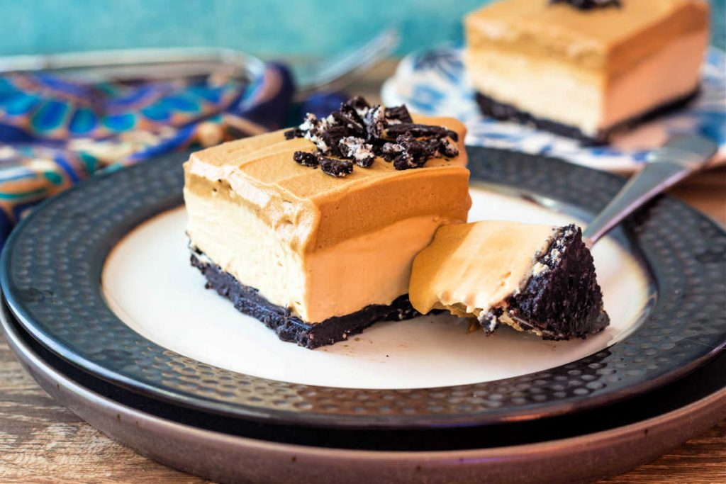 A square whipped coffee cheesecake bar on a plate with a bite of the dessert on a fork.
