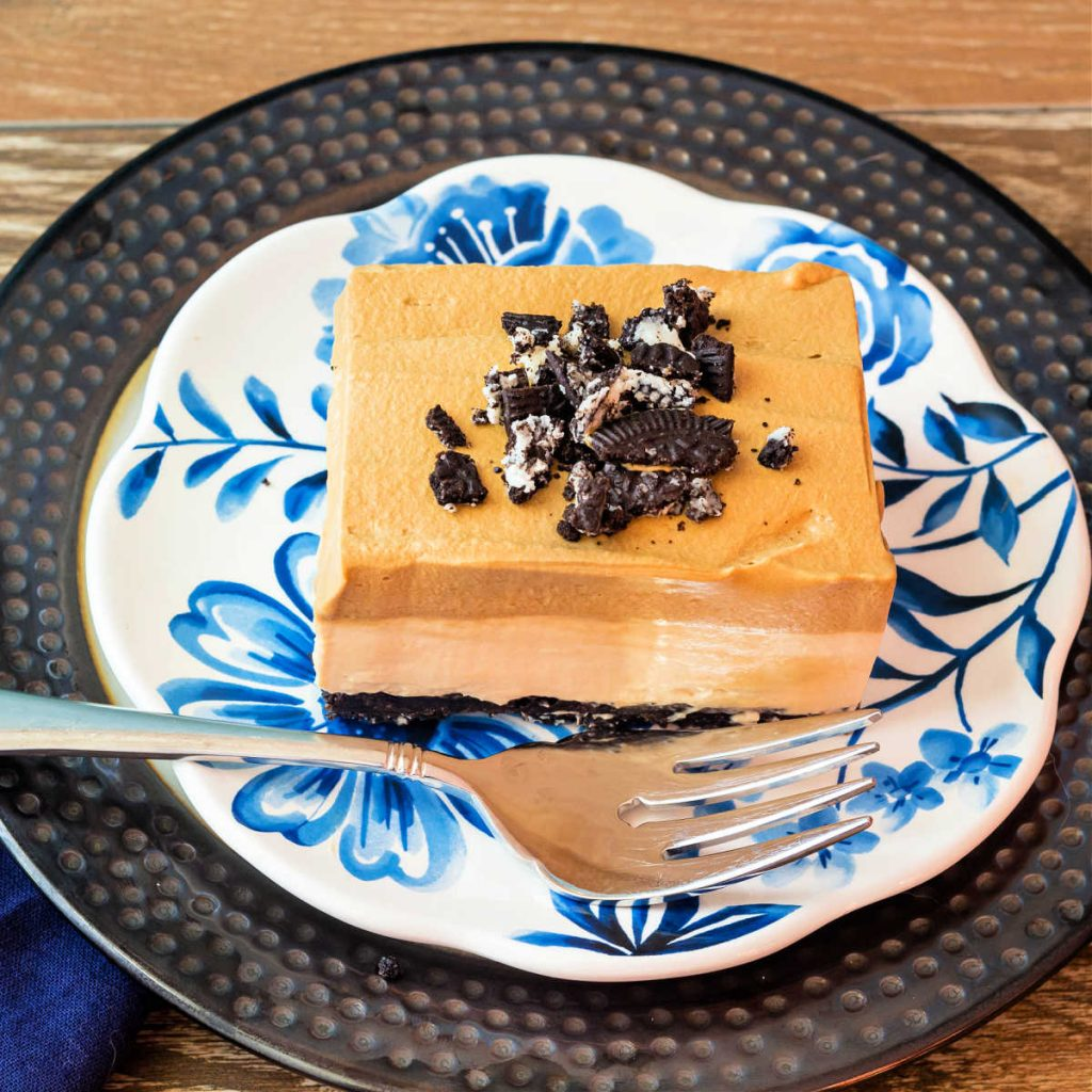 A high-angle shot of a square of no bake coffee cheesecake on a blue flowered plate with a fork.