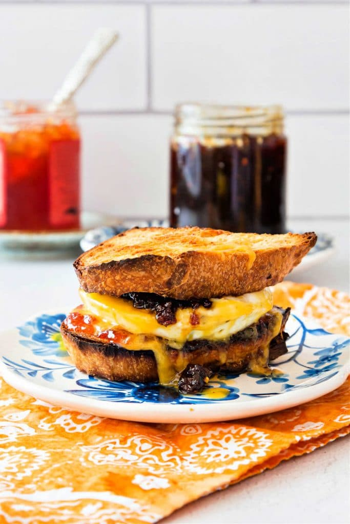 A toasted breakfast sandwich on a plate with jars of bacon jam and pepper jelly in the background.