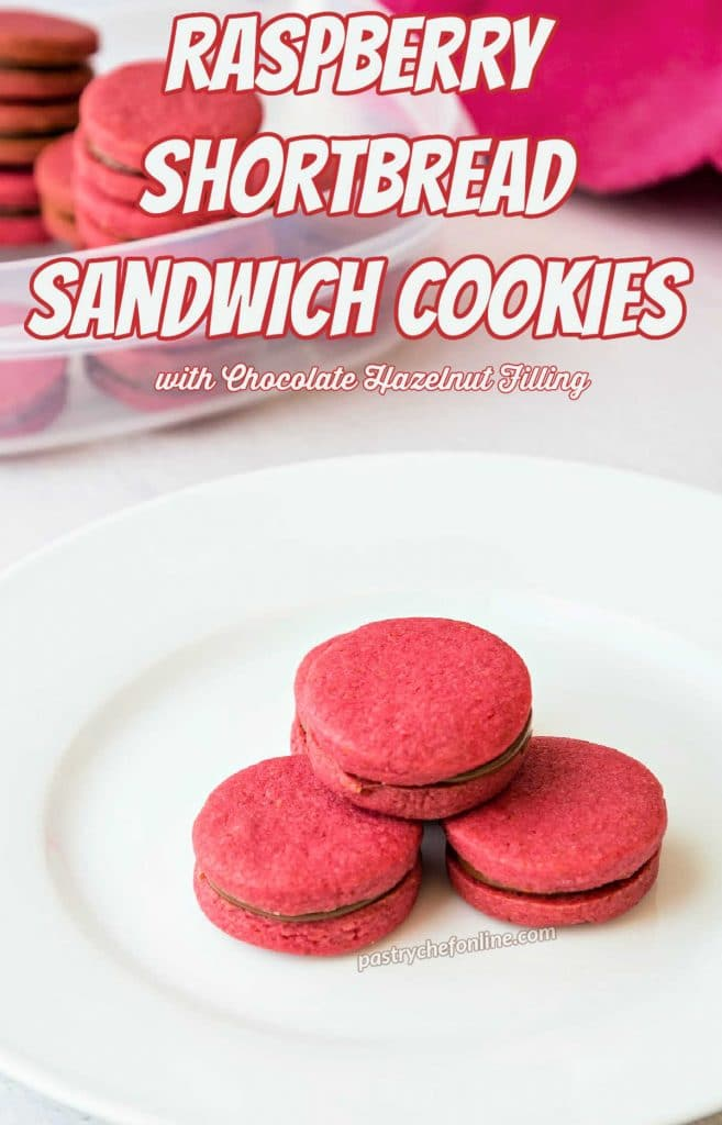 """Bright pink raspberry shortbread cookies on a white plate. Text overlay reads, """"raspberry shortbread sandwih cookies with chocolate hazelnut filling."""""""