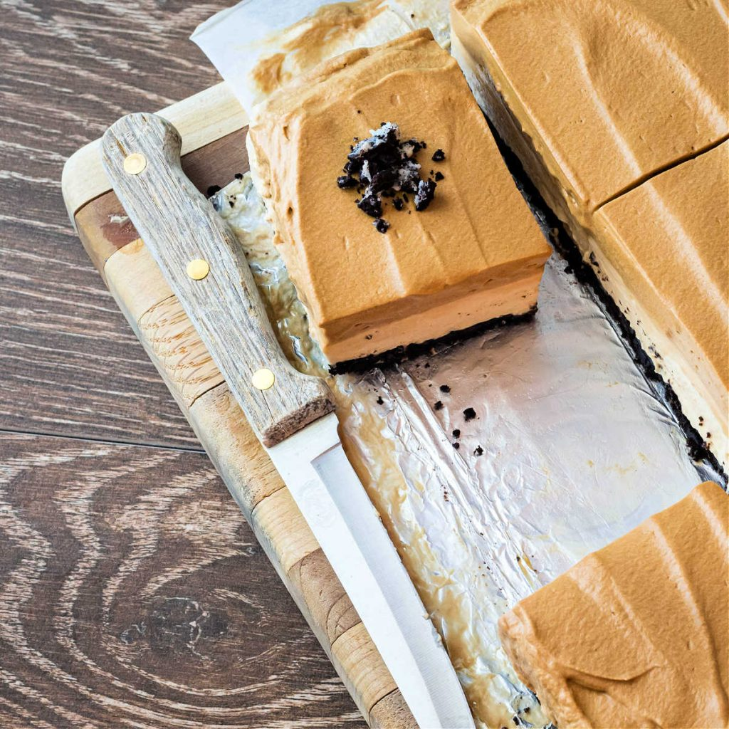 A high-angle shot of a wooden cutting board on a wooden background. On the cutting board are sliced coffee cheesecake bars, one with crushed chocolate cookies on top.