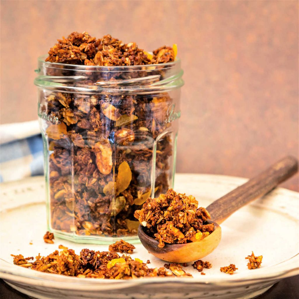 A square image of a glass jar filled with homemade granola.