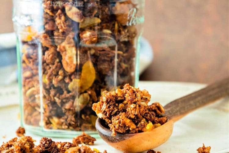 A jar of spent grain granola with chopped dried apricots in a glass jar on a beige plate.