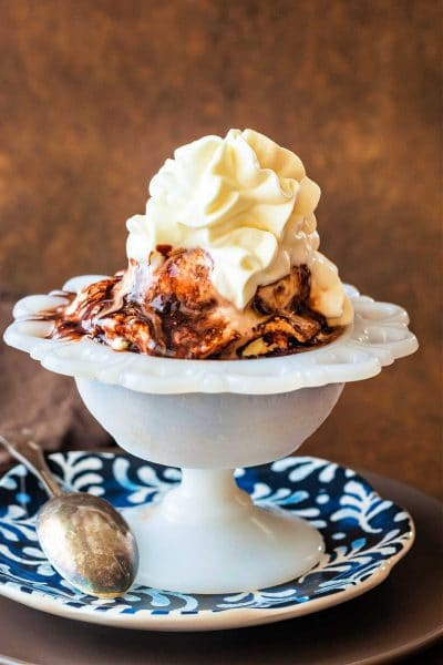 A shot of ice cream in a white dish with chocolate syrup and whipped cream on top.