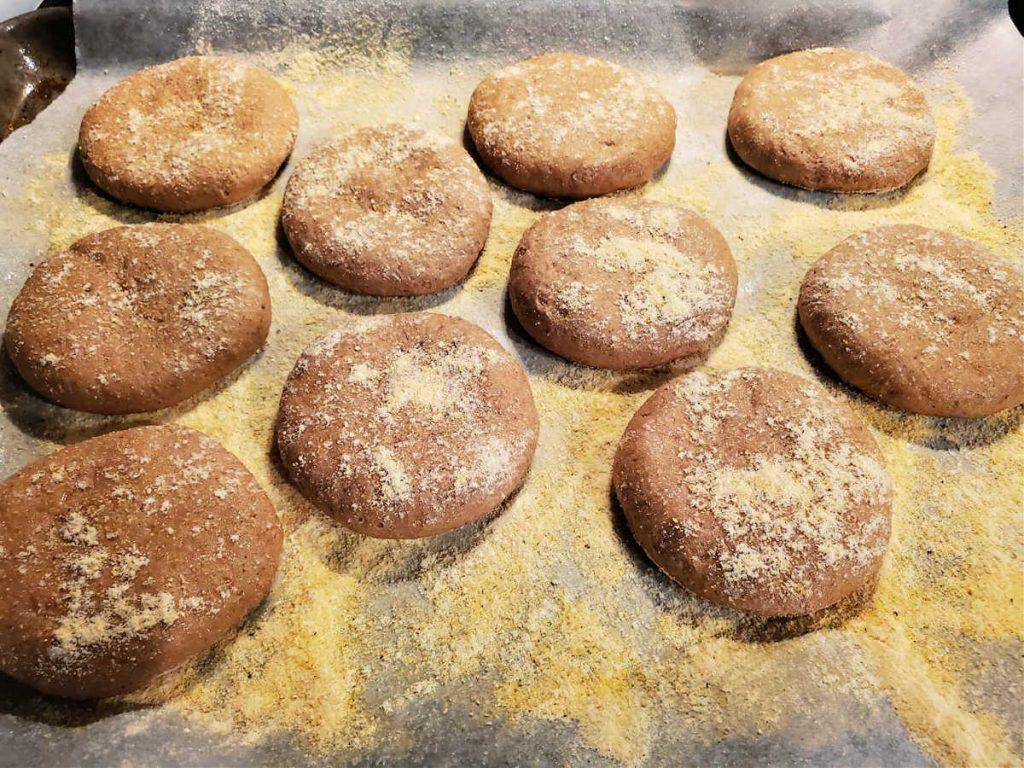 Ten discs of beige dough on a cornmeal-lined sheet pan.