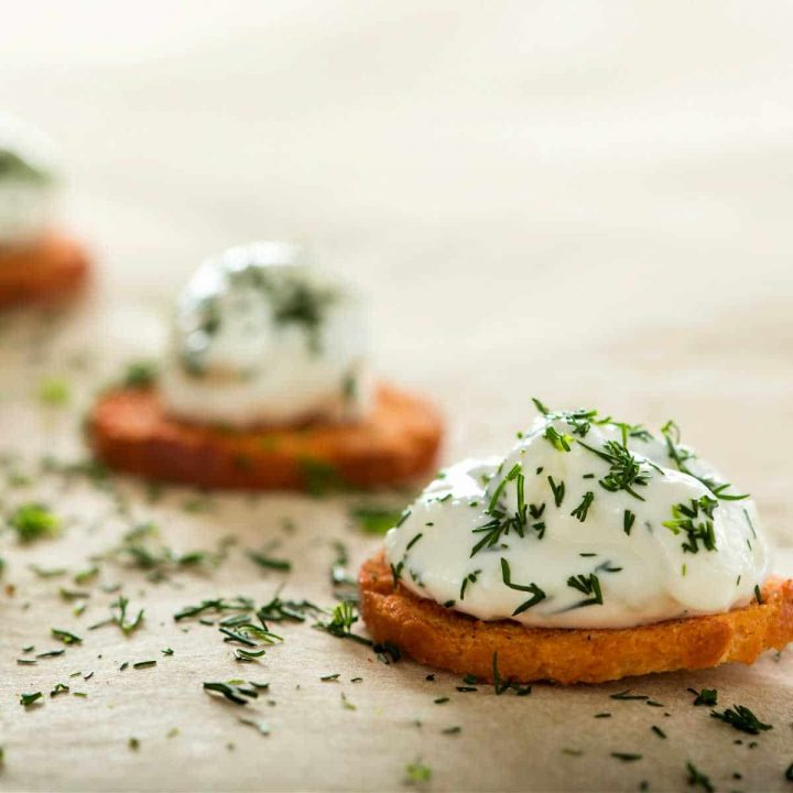 Toasted rounds of bread topped with large dollops of homemade creme fraiche and sprinkled with chopped dill.