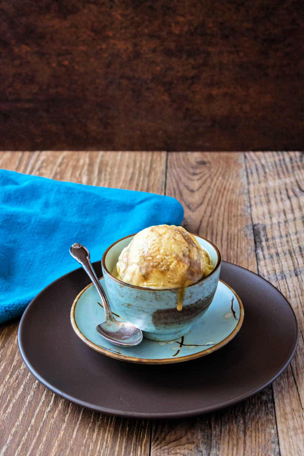 A blue bowl of butterscotch ripple ice cream on a wooden background.