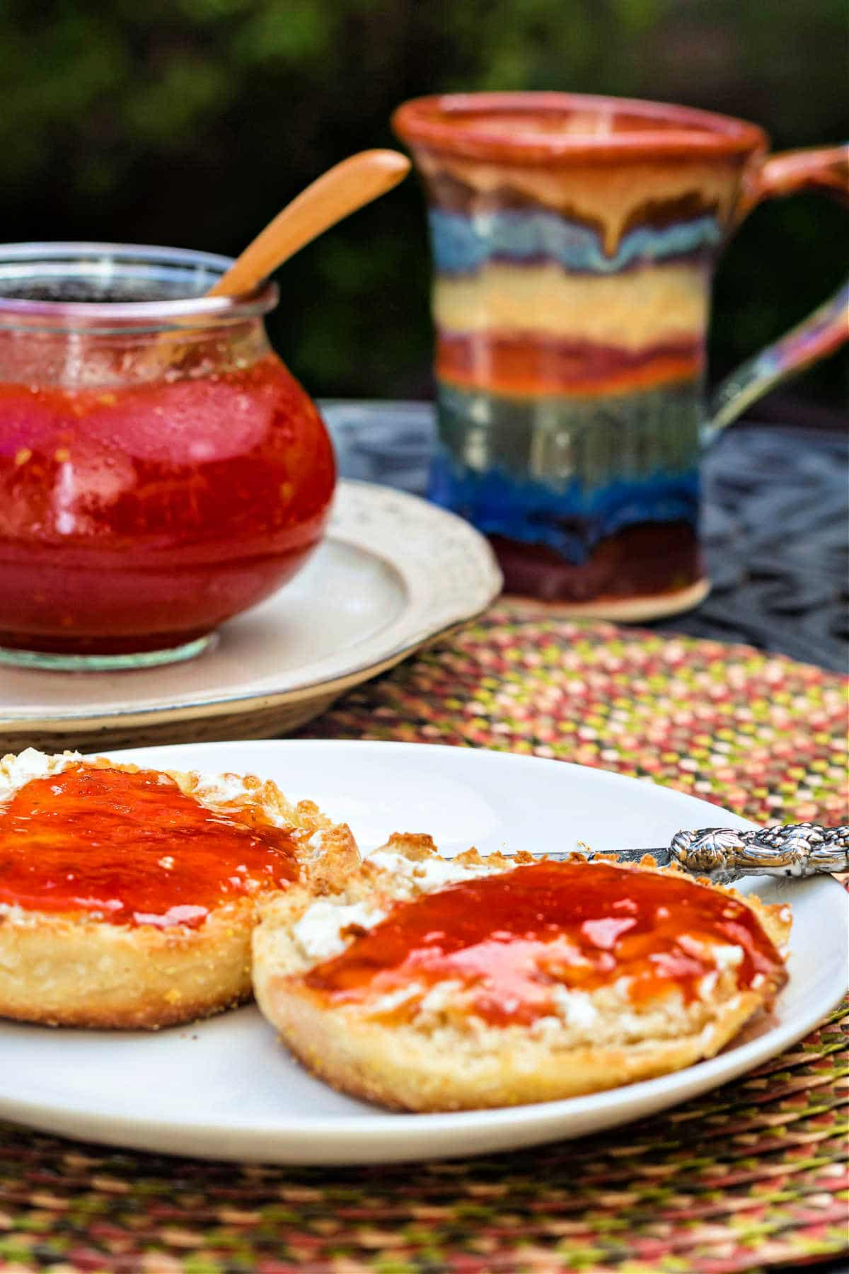 A white plate with two pieces of English muffin on it spread with jam. The jar of jam is in the background along with a multi-colored mug.