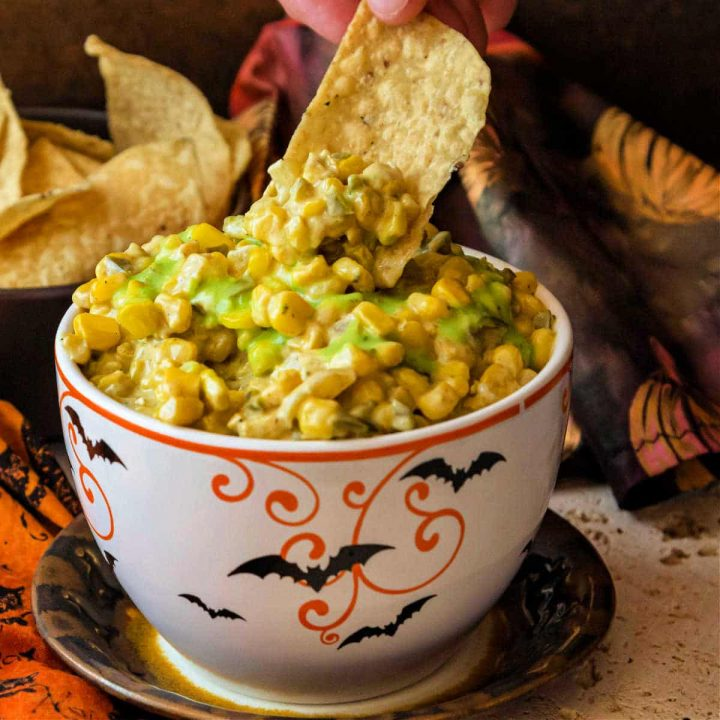 A bowl of deviled corn dotted with green salsa with a hand reaching a tortilla chip into it.