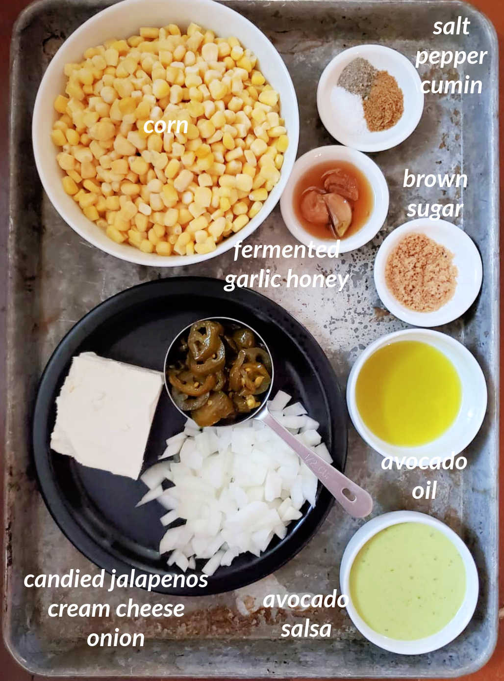 An overhead shot of all the ingredients needed to make deviled corn: corn, salt, pepper, cumin, fermented honey garlic, brown sugar, avocado oil, avocado salsa, cream cheese, candied jalapenos, and chopped onion.