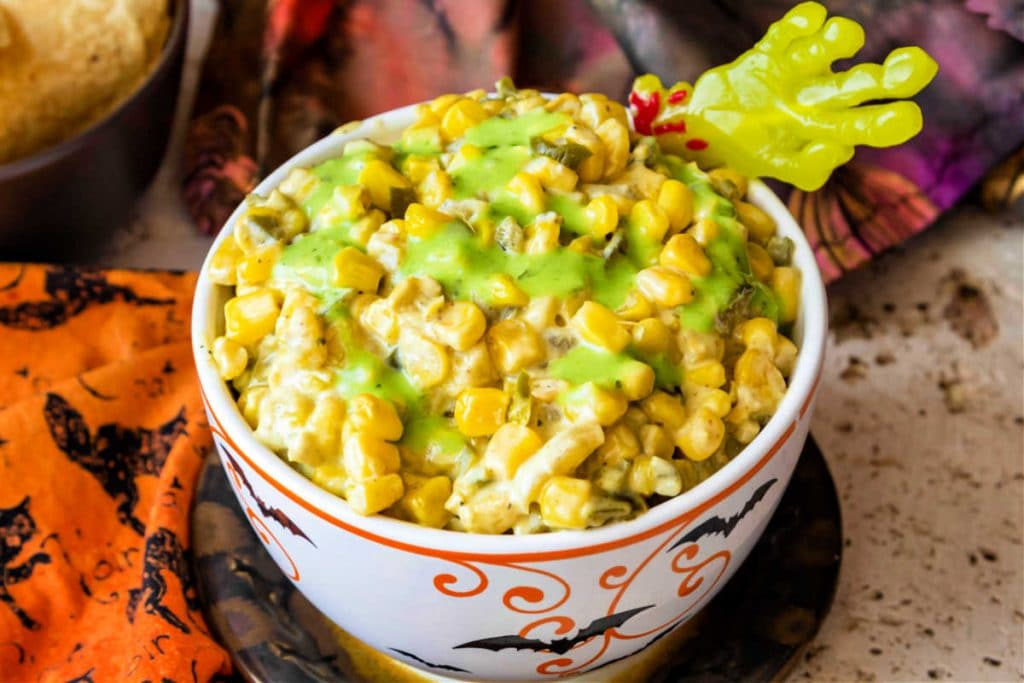 3/4 shot of white dish of creamy corn topped with a green drizzle of salsa.