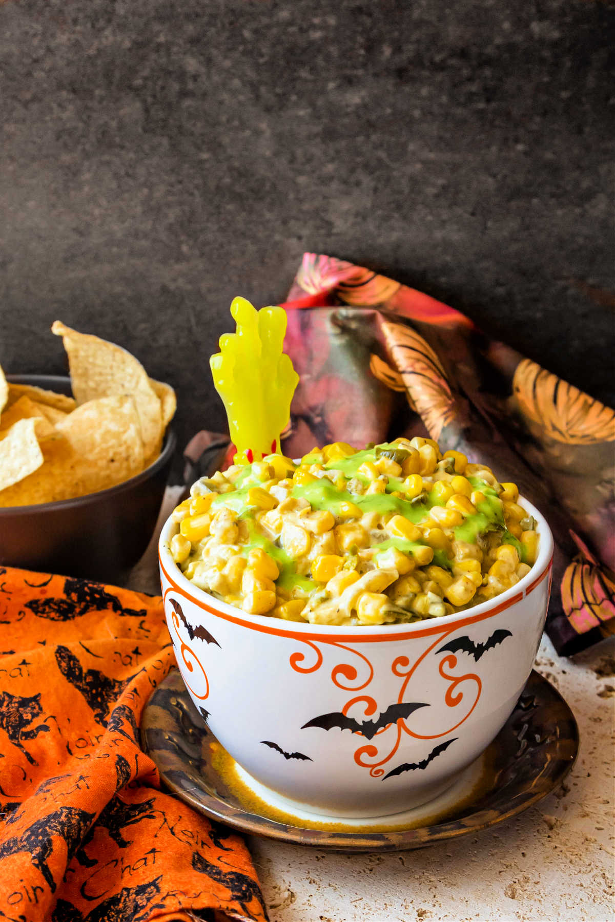 A Halloween-themed bowl of creamy corn dip topped with green guacamole salsa.